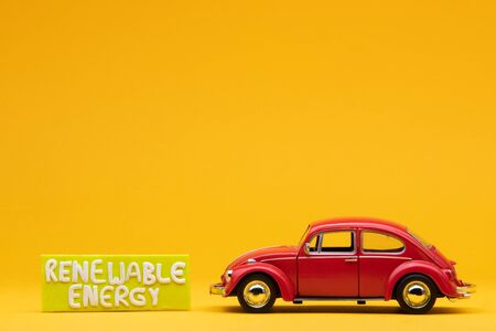 Cool red car figurine aligned to the right next to a yellow sign with the words renewable energy on it, on orange background. Stock Photo