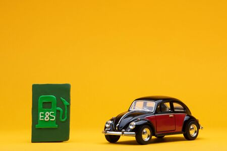 Cool crimson car figurine aligned to the right next to a pale green sign representing a filling station, on orange background.