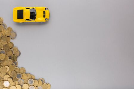An yellow car figurine next to a heap of coins, shot from above, white background.