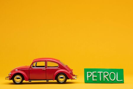 Cool red car figurine aligned to the left next to a pale green sign with the word petrol on it, on orange background.