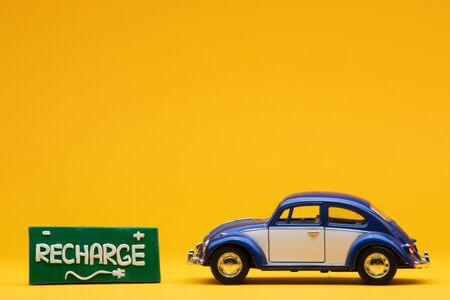 Tiny blue car figurine aligned to the right next to a green sign with the word recharge on it, on orange background.