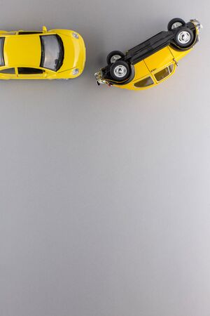 Top view of two unique yellow car figurines, aligned at the top, on gray background. 版權商用圖片