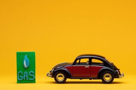 Cool crimson car figurine aligned to the right next to a green sign with the word gas on it, on orange background.