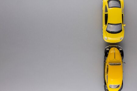 Top view of two unique yellow car figurines, aligned to the right, on gray background.