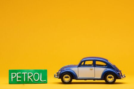 Tiny blue car figurine aligned to the right next to a pale green sign with the word petrol on it, on orange background.