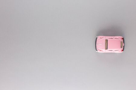 A pink car figurine, shot from above, white background. 版權商用圖片