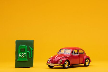 Cool red car figurine aligned to the right next to a pale green sign representing a filling station, on orange background.
