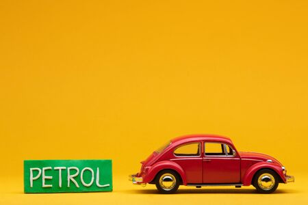 Cool red car figurine aligned to the right next to a pale green sign with the word petrol on it, on orange background.