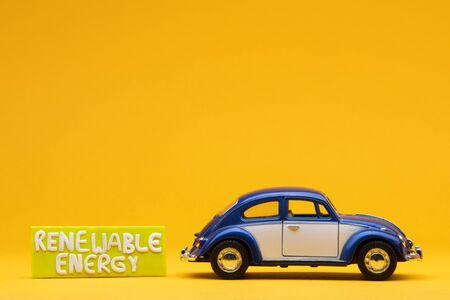 Cool blue car figurine aligned to the right next to a yellow sign with the words renewable energy on it, on orange background.
