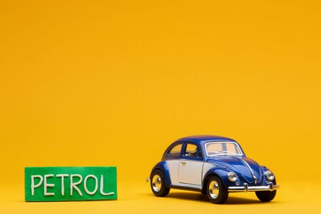 Cool blue car figurine aligned to the right next to a pale green sign with the word petrol on it, on orange background.