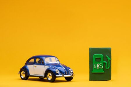 Cool blue car figurine aligned to the left next to a pale green sign representing a filling station, on orange background.