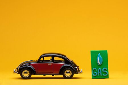 Cool crimson car figurine aligned to the left next to a green sign with the word gas on it, on orange background. Stock Photo
