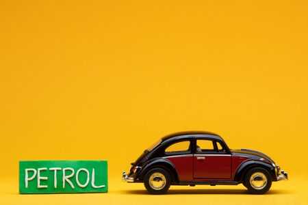 Tiny crimson car figurine aligned to the right next to a pale green with the word petrol on, on orange background.