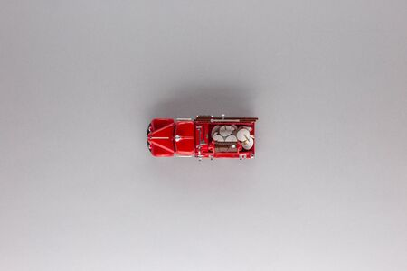 A red truck figurine, shot from above, white background, aligned in the center.