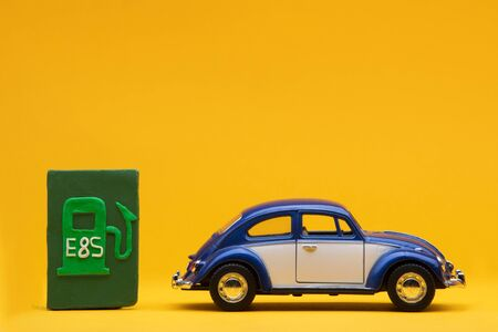 Cool blue car figurine aligned to the right next to a pale green sign representing a filling station, on orange background. Stock Photo