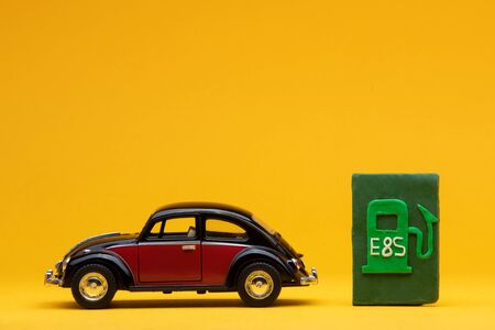 Cool crimson car figurine aligned to the left next to a pale green sign representing a filling station, on orange background. Stock Photo