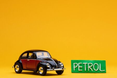 Cool crimson car figurine aligned to the left next to a pale green sign with the word petrol on, on orange background. Stock Photo