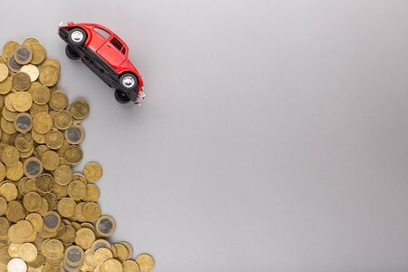 A red car figurine turned over near a heap of coins, shot from above, white background.
