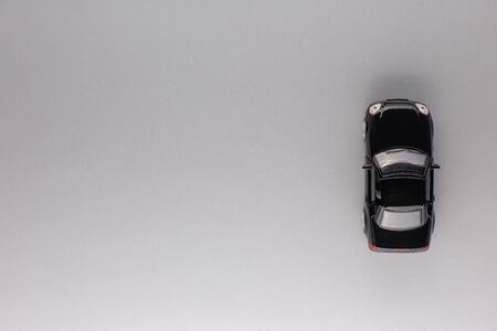 Top view of a new black car figurine, aligned to the right, on gray background. 版權商用圖片