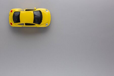 An yellow car figurine, shot from above, white background. 版權商用圖片