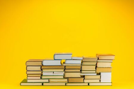 A pile of educational books on yellow background.