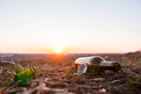 A glass bottle next to some glass shards on fertile soil at sunrise.