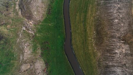 A river located in the middle of a green meadow shot perpendicularly from above Stok Fotoğraf