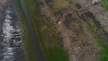 River located at the bottom of an abrupt valley shot from above. Imagens