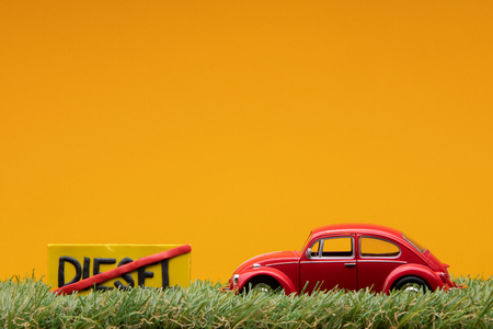 Chisinau, Moldova - August 15th 2019: A red car figurine aligned to the right on grass next to an yellow sign with the word diesel cut on it, on orange background.