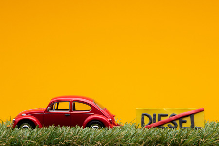 Chisinau, Moldova - August 15th 2019: A red car figurine aligned to the left on grass next to an yellow sign with the word diesel cut on it, on orange background.