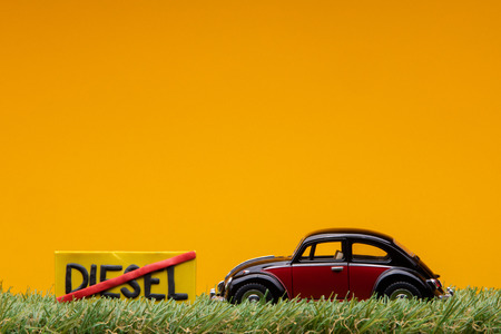 Chisinau, Moldova - August 15th 2019: A crimson car figurine aligned to the right on grass next to an yellow sign with the word diesel cut on it, on orange background. Redakční