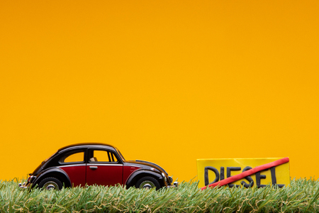 Chisinau, Moldova - August 15th 2019: A crimson car figurine aligned to the left on grass next to an yellow sign with the word diesel cut on it, on orange background. Redakční