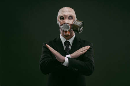 Portrait of a man wearing a dark business suit and an old gas mask with his hands x crossed, isolated on dark green background. Archivio Fotografico