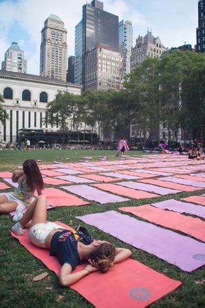 bryant: Two girls relaxing on yoga mats in Bryant Park, New York City