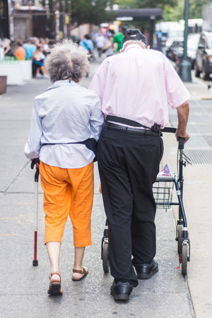 mutually: Two old people mutually supporting each other as they walking down the street in New York City