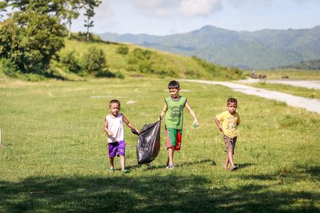 Crianças catando lixo perto Monte Pinatubo em 27 de agosto de 2017 em Santa Juliana, Capas, Central Luzon, Filipinas Editorial