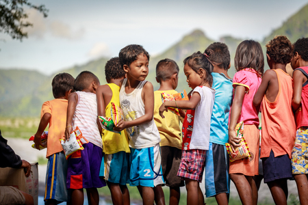 Filipino niños de pie en una línea y la celebración de aperitivo en sus manos el 27 de agosto de 2017 en Santa Juliana, Capas, Luzón Central, Filipinas