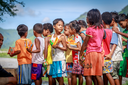 Filipino children standing in a line and holding snack in their hands on Aug 27 2017 in Santa Juliana, Capas, Central Luzon, Philippines