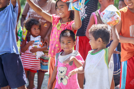 Filipino children standing in a line and holding snack in their hands on Aug 27 2017 in Santa Juliana, Capas, Central Luzon, Philippines Imagens - 85377692