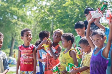 Filipino niños de pie en una línea y la celebración de aperitivo en sus manos el 27 de agosto de 2017 en Santa Juliana, Capas, Luzón Central, Filipinas Editorial