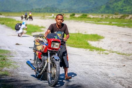 Gente filipina que monta la motocicleta a lo largo del campo volcánico cerca del monte Pinatubo el 27 de agosto de 2017 en Santa Juliana, Capas, Luzon central, Filipinas