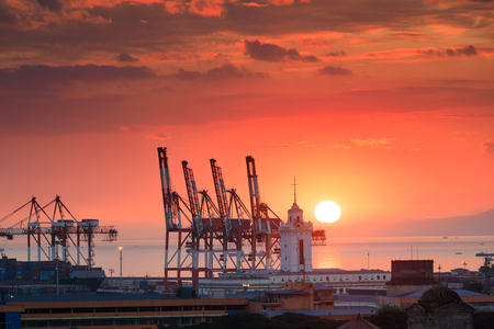 Beautiful sunset and industrial cargo cranes in Manila bay, Philippines Stock Photo