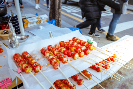 Seoul, South Korea - March 2, 2018 : Strawberry sticks covered melted sugar, Unmanned or unattended kiosk on small trailer at Hongdae (Hongik University) shopping street. 写真素材