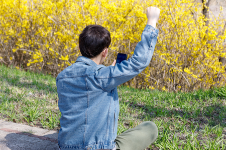 Asian man with his arms up and looking at smartphone in forsythia park Stock Photo