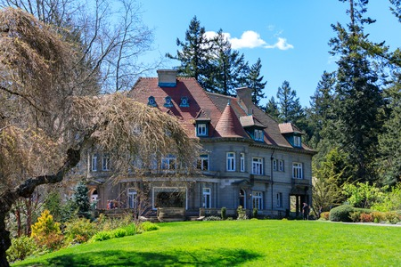 Portland, Oregon, USA - April 19, 2018 : Pittock Mansion, view on the house surrounded by trees from the garden on a beautiful sunny spring day, Portland 新聞圖片
