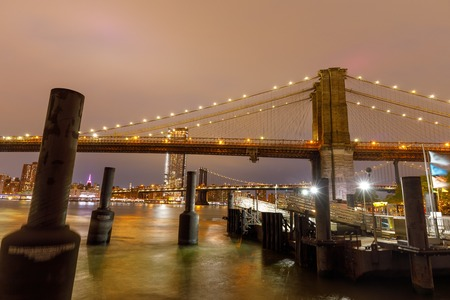 Brooklyn Bridge over hudson river in New York City at sunset.