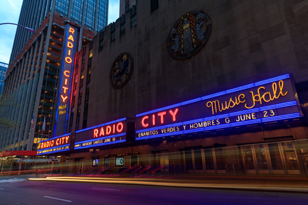 New York, USA - May 6, 2018 : Corner of Radio City Music Hall, theater building at Rockefeller Center, modern architecture with billboards. Entertainment and tourist destination.