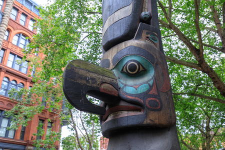Seattle, Washington - June 30, 2018 : Face of Tlingit totem pole on Pioneer Square in Seattle. Pioneer Square was city center where founders settled in 1852. Editorial