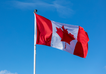 Canada flag waving against a blue sky