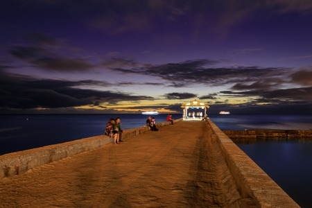 Honolulu, Hawaii - Dec 25, 2018 : Waikiki Beach walls pier at a golden hour sunset